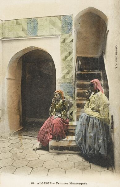 An attractive hand-tinted postcard depicting two Moorish Women sitting and standing at the bottom of a narrow set of stairs leading to the upper level of a house