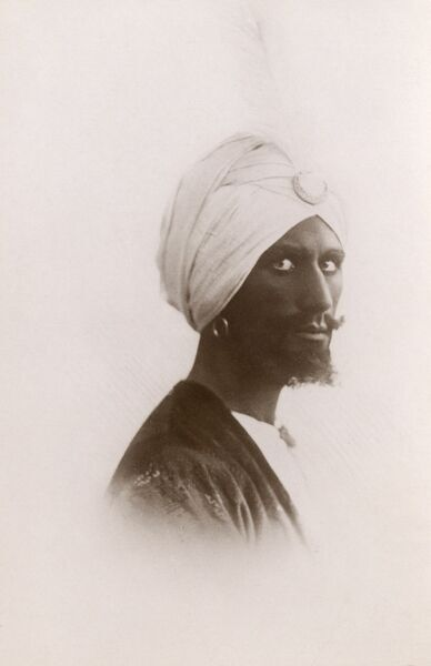 Moroccan Man (Arab) wearing a white turban and sporting a particularly piercing gaze and very nicely trimmed goatee beard. Date: circa 1909