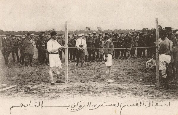 French Troops based in Morocco take part in an athletics competition. This card shows the high jump (from a standing start) competition in full flow. Local Moroccan men are acting as the bar attendants. Date: circa 1920
