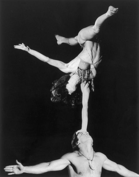 A female acrobat skillfully balances on one arm on a male acrobat's head. Photographed when the circus was visiting Cornwall, England