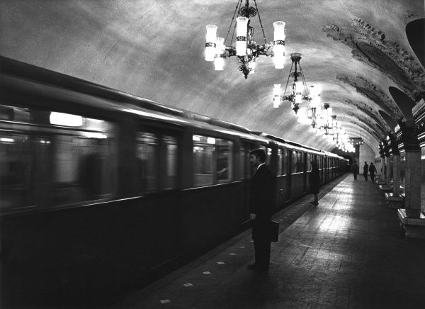 A business man commuter, about to board an underground train, which has just arrived on the platform of a Rococo style tube station, Moscow, Russia. Date: late 1960s