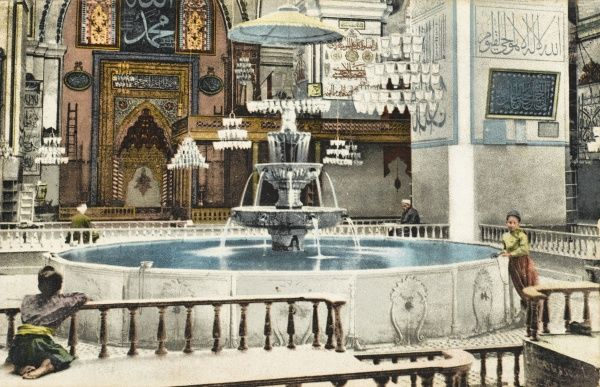 The lavish interior of a Mosque in Constantinople, Turkey with an ornate fountain and hanging chandeliers