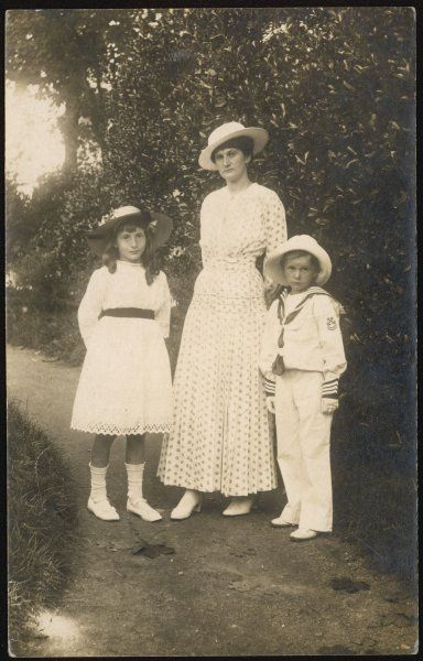 A rather serious-looking mother with her son and daughter on a garden path. Date: early 20th century