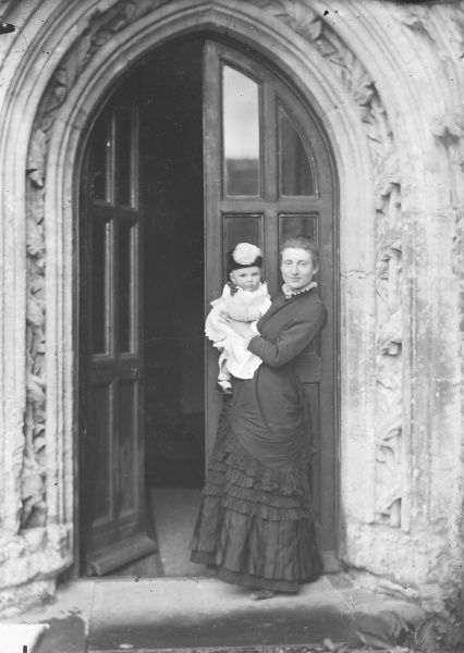 A mother stands on the step in the half- open doorway of a grand entranceway holding her baby