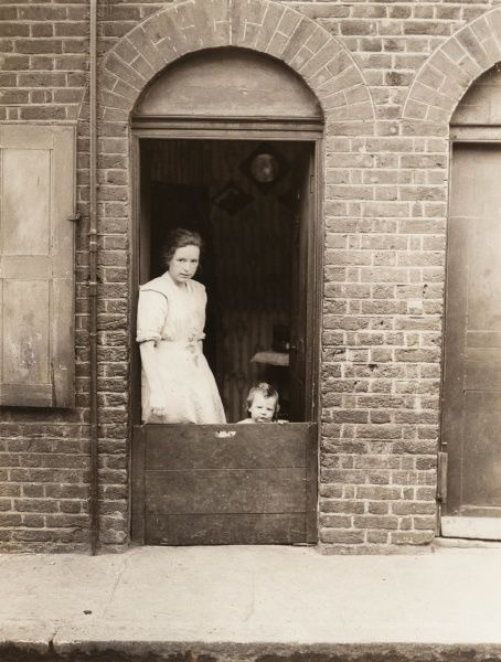 A mother stands with her child at the door of her home in Limehouse, east London : the boards are presumably to prevent the child straying into the street