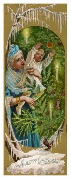 A mother holds up her child to see the baubles on the tree