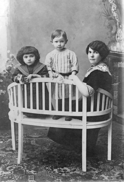A mother and her two children pose for their photograph on a wooden bench. The girl on the left is wearing a sailor dress. The child standing in the middle looks like a boy, but is probably a girl with very short hair, wearing a pleated dress with a belt