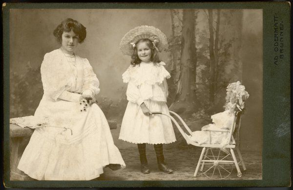 Mother, daughter and doll pose for their photograph in the studio