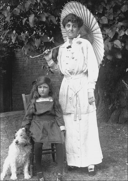 A Mother and daughter pose for a photograph in a garden in Devon in the 1910s. The lady holds an elegant Chinese-style parasol and the seated young girl is staying close to the small family pet dog. Photograph by Ralph Ponsonby Watts
