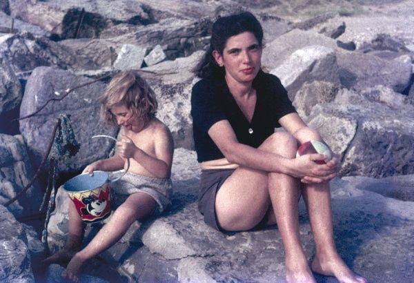 A mother and her daughter sit on the rocks at a seaside resort. The little girl is trying to mend the handle on her bucket, which has a picture of Mickey Mouse on it