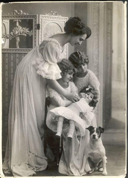 An Edwardian mother wears a soft, flowing gown with frills at the neckline, sleeves and hem while the daughters' dresses are decorated with a profusion of lace