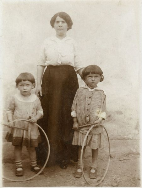 A mother and her two daughters pose for their photograph. Each girl has a hoop and stick, a popular game at the time. They are from the settlement of Kostel (also known as Podivin) in South Moravia, now in Czechoslovakia