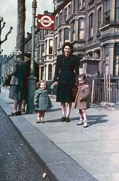 A mother and her two daughters waiting for a No.6 bus at Shirland Road, Maida Vale, London W9. They are all smartly dressed, but the houses in the background are showing postwar shabbiness