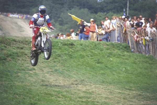 Doing a 'wheelie' on a motorcycling motocross circuit. Date: 1980