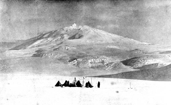 Photograph showing Mount Erebus, the 13,200 foot volcano, that towers over Ross Island, Antarctica. This picture was taken during the National Antarctic Expedition of 1901-04 and shows one of the expedition's camps in the foreground. Date: 1909