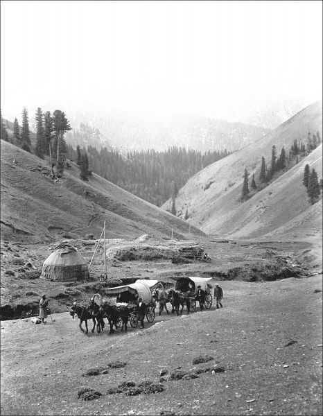 A mountain scene, showing people travelling in horse-drawn wagons, in Kashgar, western China. Photograph by Ralph Ponsonby Watts