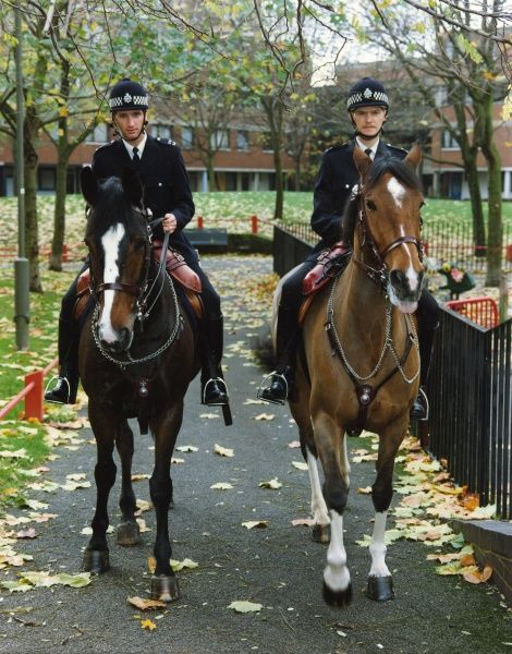 Two mounted Metropolitan Police Officers on patrol through an inner London Council Estate