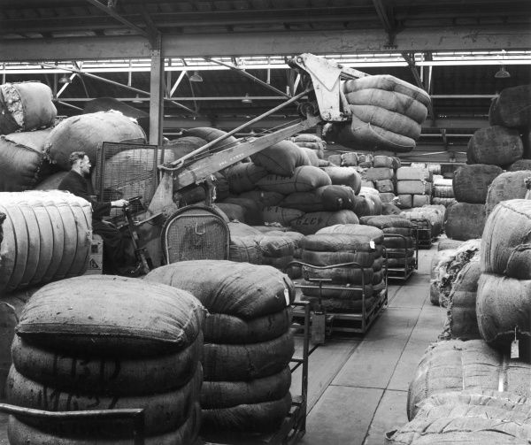 An operator uses a small picker to stack and manoeuvre piles of sacks, containing cotton or wool, into place in a large warehouse. Photograph by Heinz Zinram