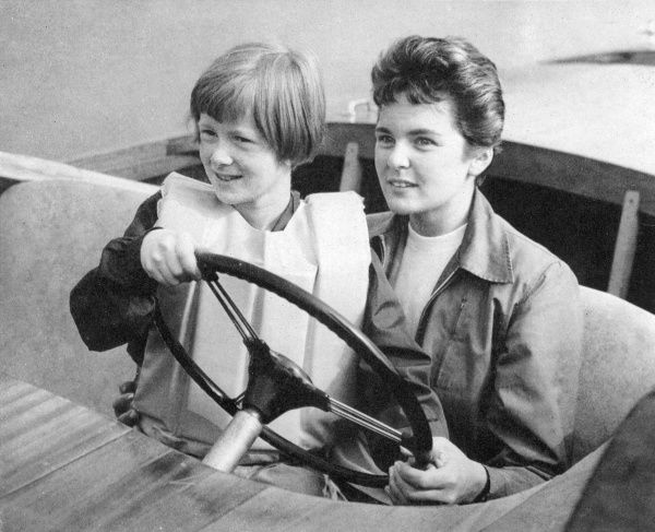 Georgina, the ten year old daughter of Mr Donald Campbell, helps her mother take the wheel of their launch on Coniston Water, Lancashire, the day that her father broke his own speed record with a new one of 225.63 m.p.h. with his jet-engined boat Bluebird
