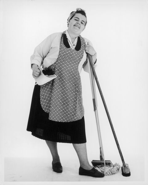 'Mrs. Mop', the quintessential charlady, equipped with her pan and brush, mop, 'squeegy', headscarf and apron on... Date: 1960s