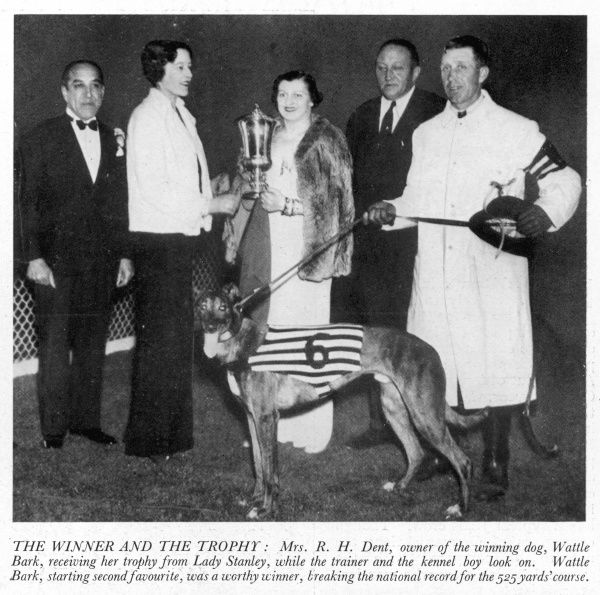 Wattle Bark, winner of the 1937 Greyhound Derby at White City is picture with his owner, Mrs. R. H. Dent receiving her trophy from Lady Stanley while the trainer and the kennel boy look on. Wattle Bark, starting second favourite, was a worthy winner