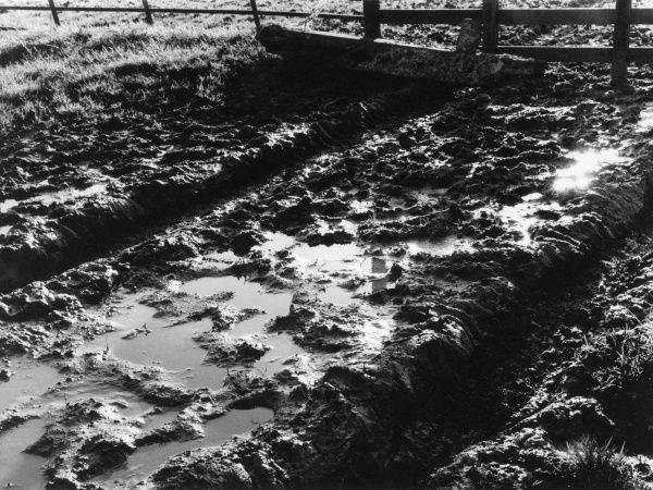 A muddy, waterlogged, country lane, following a heavy downpour of rain. Date: 1960s