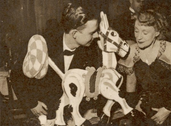 Peter Thompson, producer of BBC television's Children's Hour, and Annette Mills with the popular puppet character Muffin the Mule at the National Television Fund Ball at the Dorchester Hotel in London