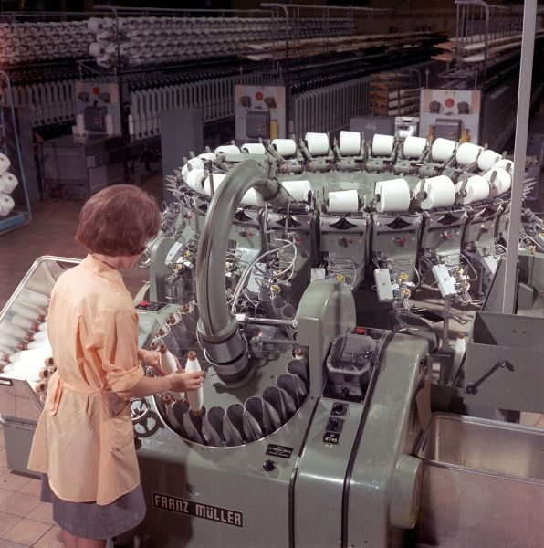 A factory worker operates a Muller automatic cone-winding machine, (used for clearing and winding single-spun yarns) at Patons & Baldwins factory in Darlington. Patons & Baldwins was a leading British manufacturer of knitting yarn.Photograph by Heinz Zinram
