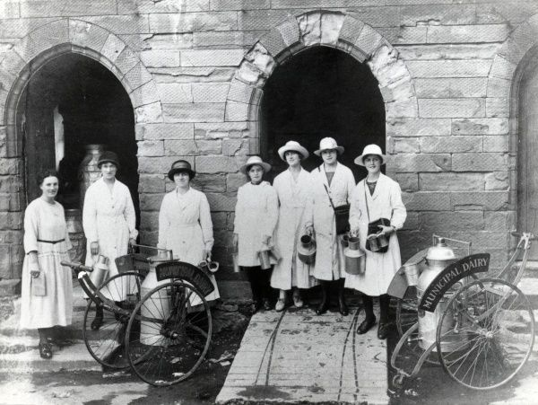 A group of seven women working for the Municipal Dairy pose outside the dairy building, somewhere in South Wales. Two churn wagons, each one holding a large milk churn, can be seen in front of them. The women hold smaller churns in their hands