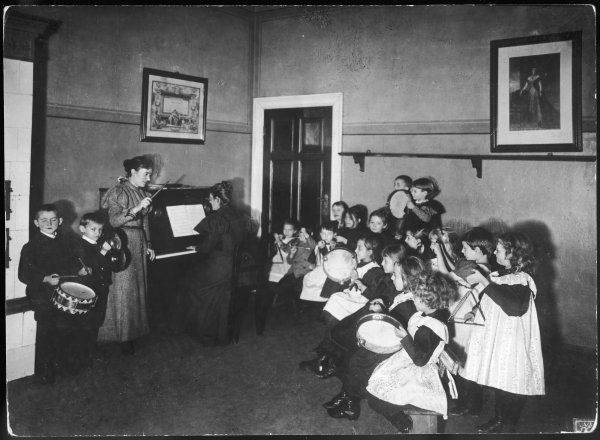 A music lesson at a German school. One teacher plays the piano while another conducts the schoolchildren, who play an assortment of instruments, including tambourines, etc