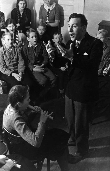 An enthusiastic music teacher encourages his pupils to sing a rousing chorus accompanyment to a girl playing a recorder. Date: early 1930s