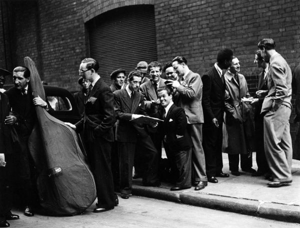 A group of musicians (identifiable by the large double bass carried by one man, and a record discussed by some others) gathered together in an unidentified London street in the late 1940s