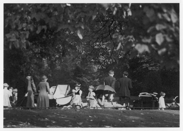 Well-to-children with their Nannies, probably in a London park