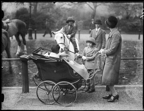 A fashionable young mother, pushing her baby in its splendid pram, stops to pass the time of day with some horse riders on Rotten Row, Hyde Park, central London