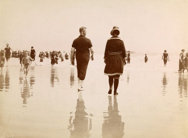 Bathing, Narragansett Pier. Man & woman walking in the surf on the beach at Narragansett, R.I., dressed in bathing suits