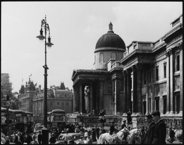 Busy scene outside the National Gallery, photographed from the steps of St. Martin- in-the-Fields, including mounted policemen and Routemaster buses