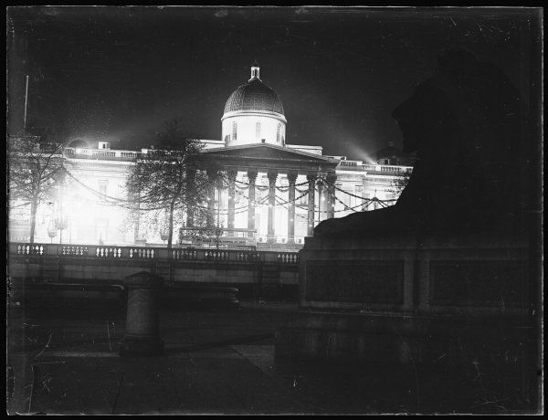 The exterior of the National Gallery, Trafalgar Square, London, floodlit at night for dramatic effect