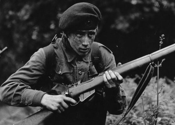 A young cadet on National Service with a rifle and a camouflaged face, perhaps taking part in a training exercise or on manoeuvres
