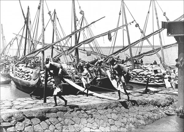 Native men unloading cargo from boats, in an unidentified location. Photograph by Ralph Ponsonby Watts