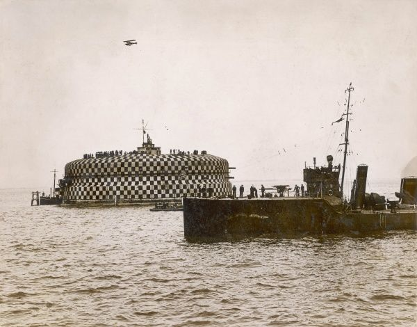 An aeroplane flying over one of the Spithead forts, with a torpedo boat destroyer in the foreground. The Fleet Review is a British tradition, in which the reigning monarch reviews the massed Royal Navy. It is thought to date back to the 15th century