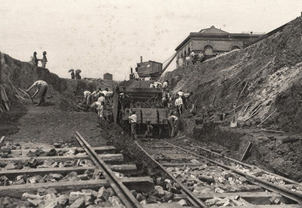 Navvies building a new railway line at an unidentified location in the UK. A station building can be seen in the top right