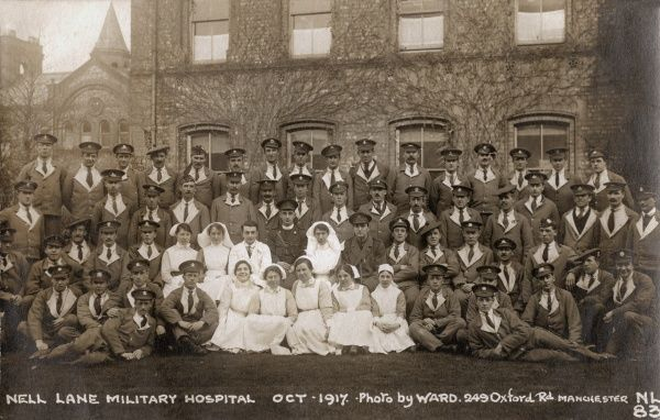 A group of uniformed military personnel and nurses pose in front of the Nell Lane Military Hospital, Withington, Manchester