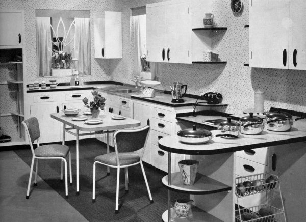 A smart Nevastane kitchen from 1957 featuring an L-shaped unit, Majestic table and chairs and various cabinets. Also visible is a Colorama pan set, a coffee percolator, a Westclox clock, and a broom cupboard