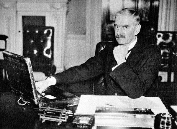 Photograph of (Arthur) Neville Chamberlain (1869-1940) at his desk with the famous briefcase, as Chancellor of the Exchequer