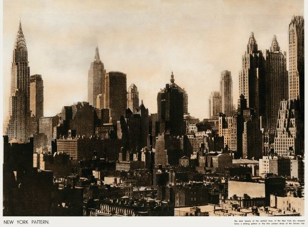 The skark beauty of the vertical lines of the New York scrapers forms a striking pattern in this fine camera study of the famous city. Date: 1937