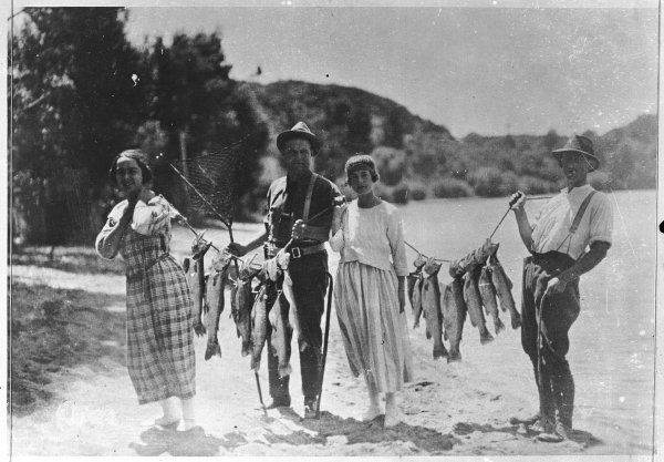 New Zealand fishermen and women proudly show off their line of freshly caught trout!