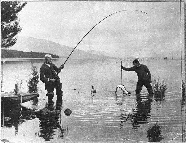 Two New Zealand trout fishermen in waders, one holding a fishing rod, the other harpooning the catch