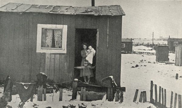 Miners' dwellings outside Newcastle, Northumberland. A mother, baby and small child stand at the door of one of the tiny, dilapidated and insanitary wooden sheds for which they pay a rent of seven shillings a week. Date: circa 1936