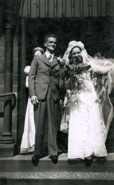 A newly married couple appear on the church steps on their wedding day. Date: circa 1930s