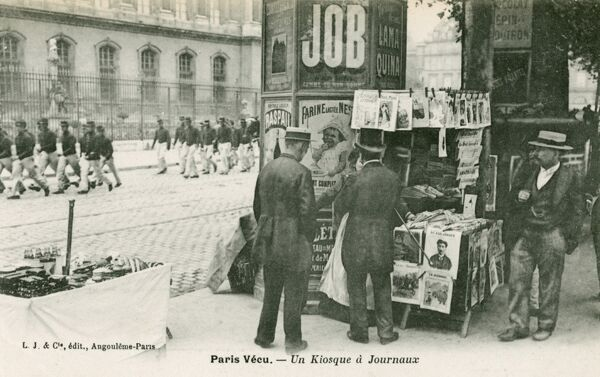 A newspaper kiosk in Paris - set up against a typical advertising poster post. A battalion of soldiers march past in the background